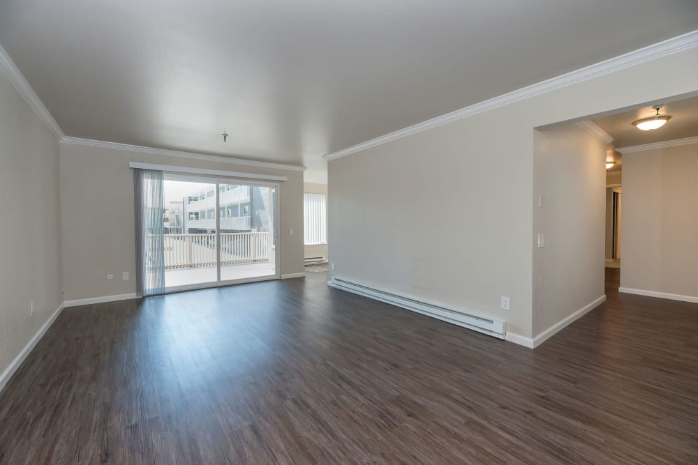 Open living room with wood-style flooring at Tower Apartment Homes in Alameda, California