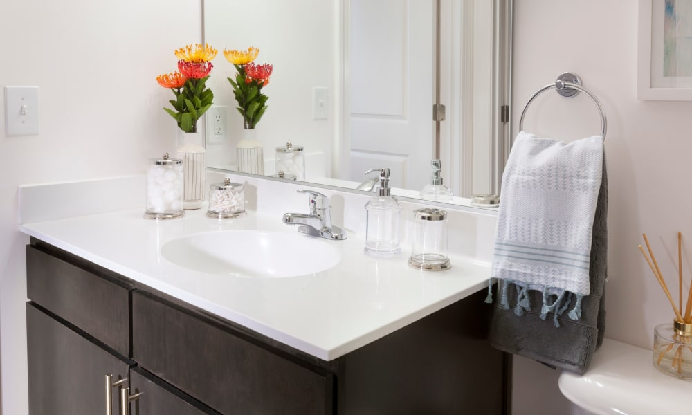 Quartz countertop and a large vanity mirror in a model home's bathroom at The Bixby in Washington, District of Columbia