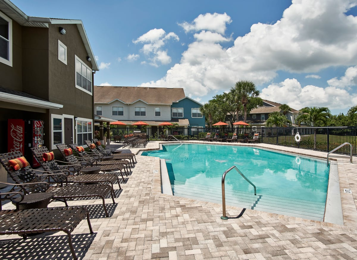 A swimming pool with lounge chairs at Calais Park Apartments in St Petersburg, Florida