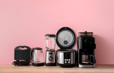 kitchen appliances against a pink wall on wooden counter