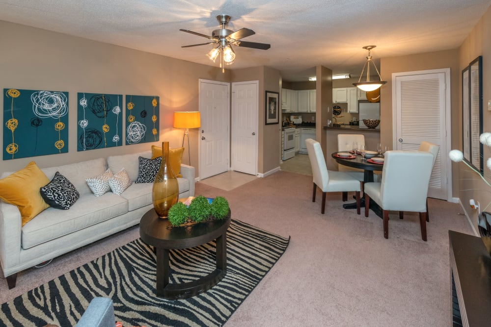 Well-decorated living space with a ceiling fan looking into the dining and kitchen areas of a model home at Bellingham Apartment Homes in Marietta, Georgia