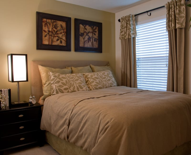 Well-furnished bedroom with an accent wall in a model home at Abaco Key in Orlando, Florida