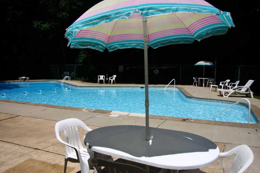 Table with umbrella by the pool at Park Apartments