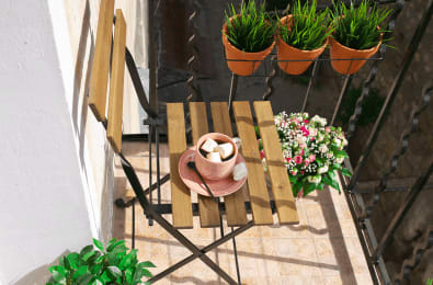 patio chair with coffee in a pink mug next to potted plants