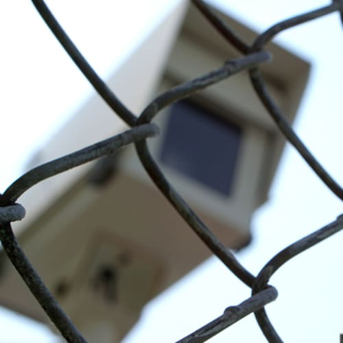 Security camera behind barbed wire fence at Red Dot Storage in Zion, Illinois