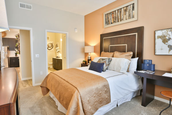 Well-decorated bedroom with accent wall and en suite bathroom in model home at Slate Scottsdale in Phoenix, Arizona