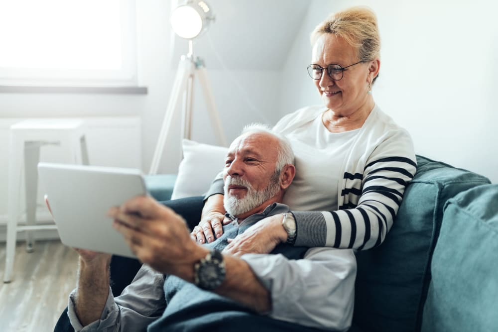 Residents looking at a tablet on their couch at Sonoma Palms in Las Cruces, New Mexico