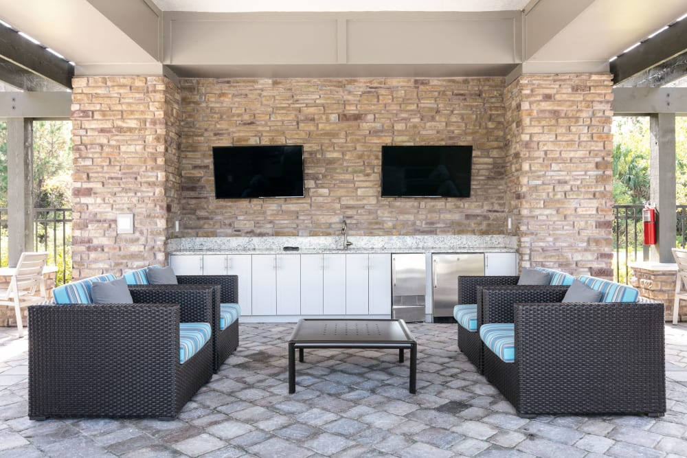 Outdoor lounge with comfortable seating and TVs at Integra 289 Exchange in DeBary, Florida