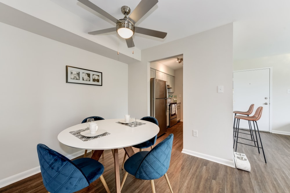 A dining room with a ceiling fan and wood-style flooring at The Landings I & II Apartments in Alexandria, Virginia