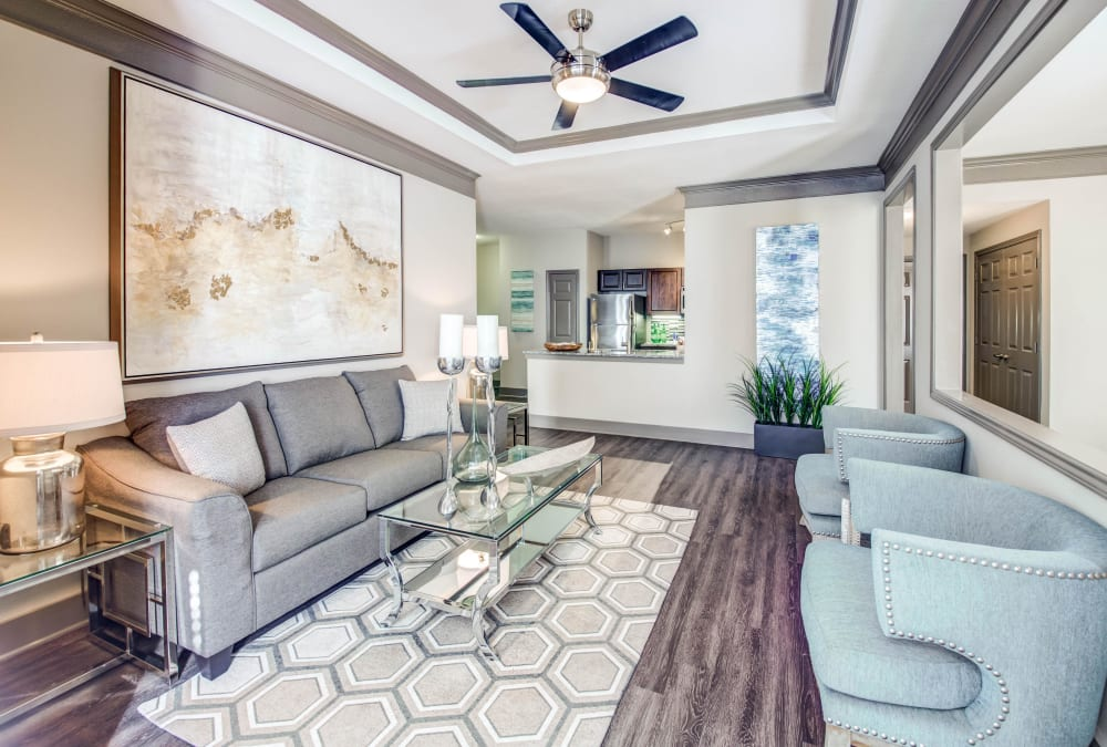 Open-concept floor plan with hardwood floors and ceiling fan in the living area of model home at Beck at Wells Branch in Austin, Texas