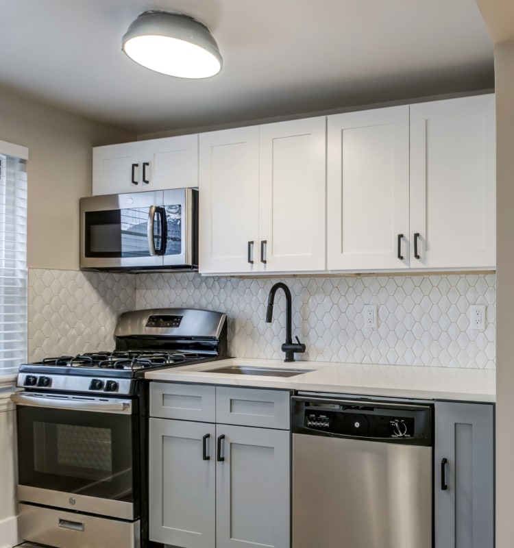 Modern kitchen with a custom tile backsplash and stainless-steel appliances in a model home at Haven New Providence in New Providence, New Jersey