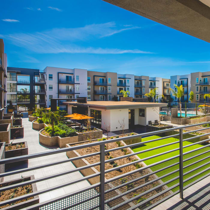 View of onsite dog park, swimming pool, and outdoor seating in common areas from upper floor at IMT Sherman Circle in Van Nuys, CA