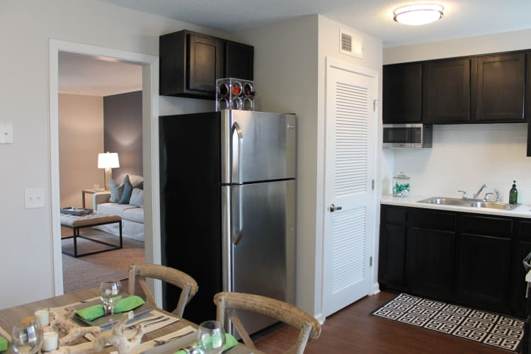 Hardwood floors, dark wood cabinetry, and stainless-steel appliances in model home at Palmilla Apartments