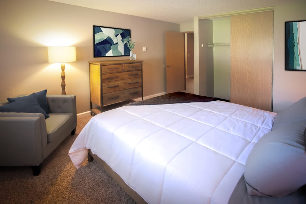 Large bed in carpeted bedroom with sitting chairs at Terra Apartment Homes in Federal Way, Washington