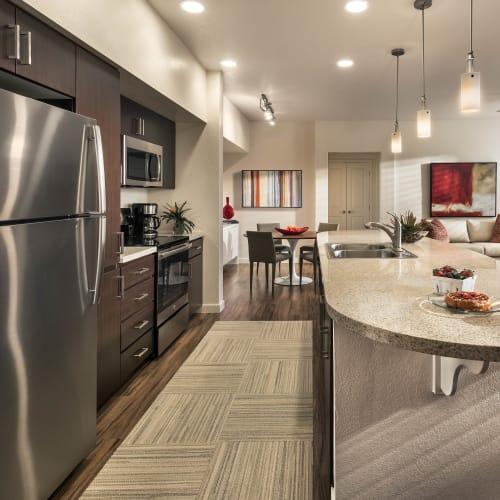 Gourmet kitchen with an island and granite countertops in a model home at Vistara at SanTan Village in Gilbert, Arizona