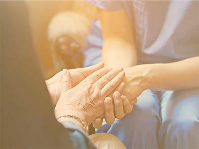 Resident and caretaker holding hands at Avenir Senior Living in Scottsdale, Arizona.