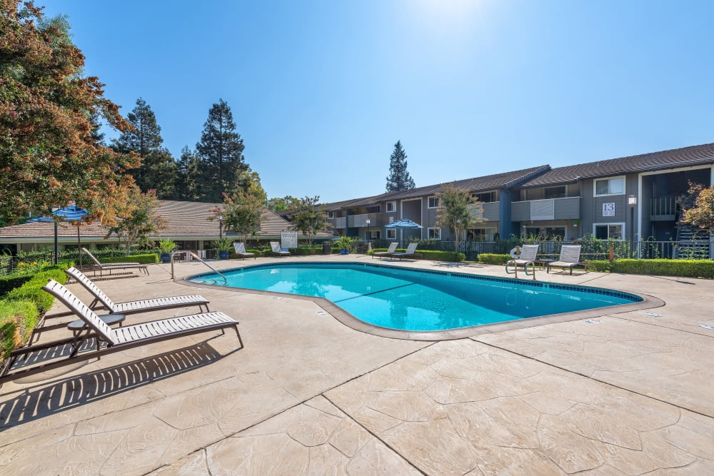 A swimming pool with a large sundeck at Shadow Oaks Apartment Homes in Cupertino, California