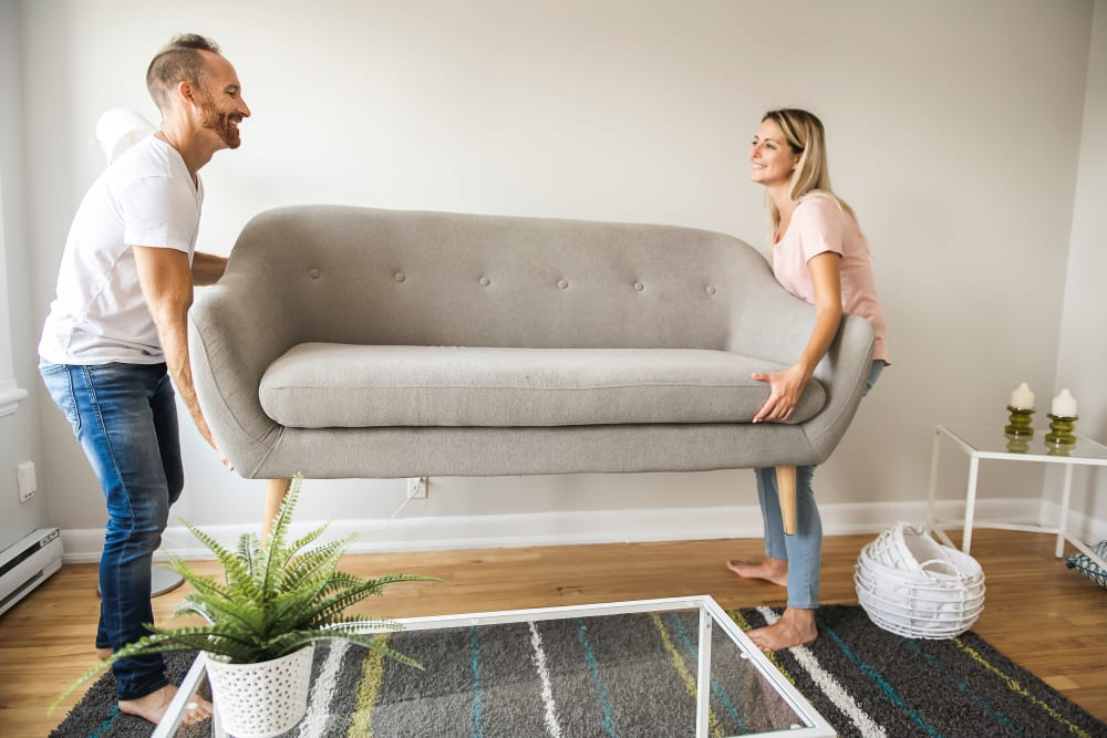 Couple moving a couch in preparation for storage in Spring, Texas at Devon Self Storage