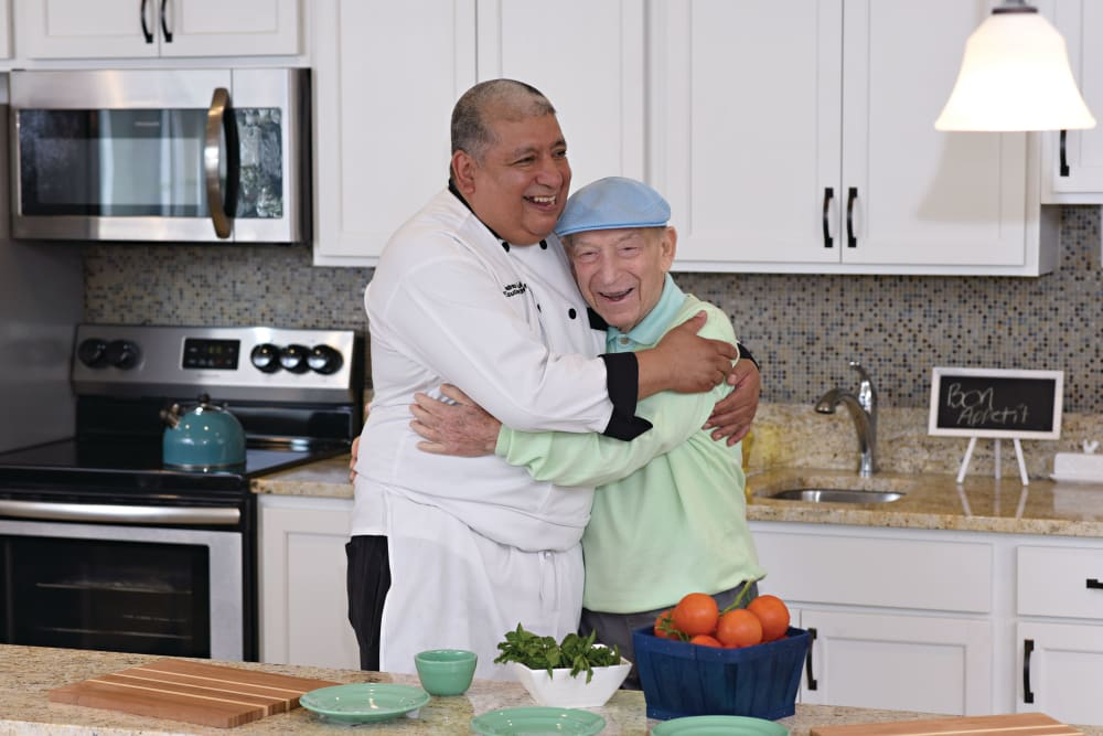 Resident and chef hugging at Elegance at Novato in Novato, California
