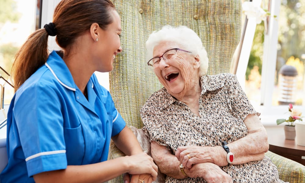 Resident and caregiver laughing at White Oaks in Lawton, Michigan