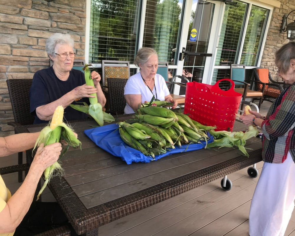 Resident shucking corn at Edencrest at The Legacy in Norwalk, Iowa.