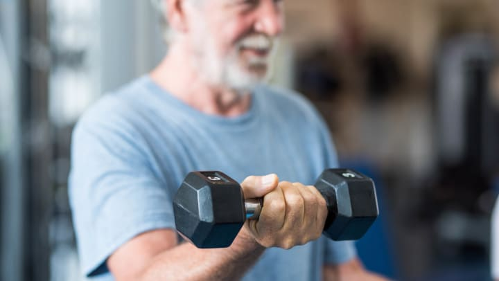 Image of a man using a hand weight to do bicep curls.