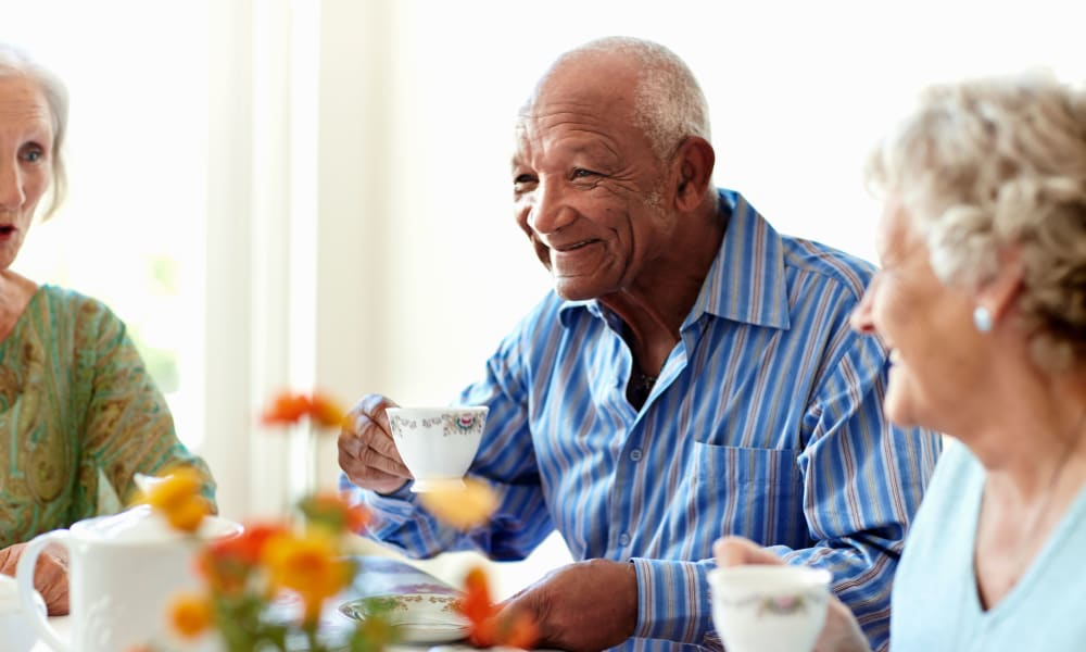 memory care resident enjoying tea with friends at Randall Residence of Sterling Heights in Sterling Heights, Michigan