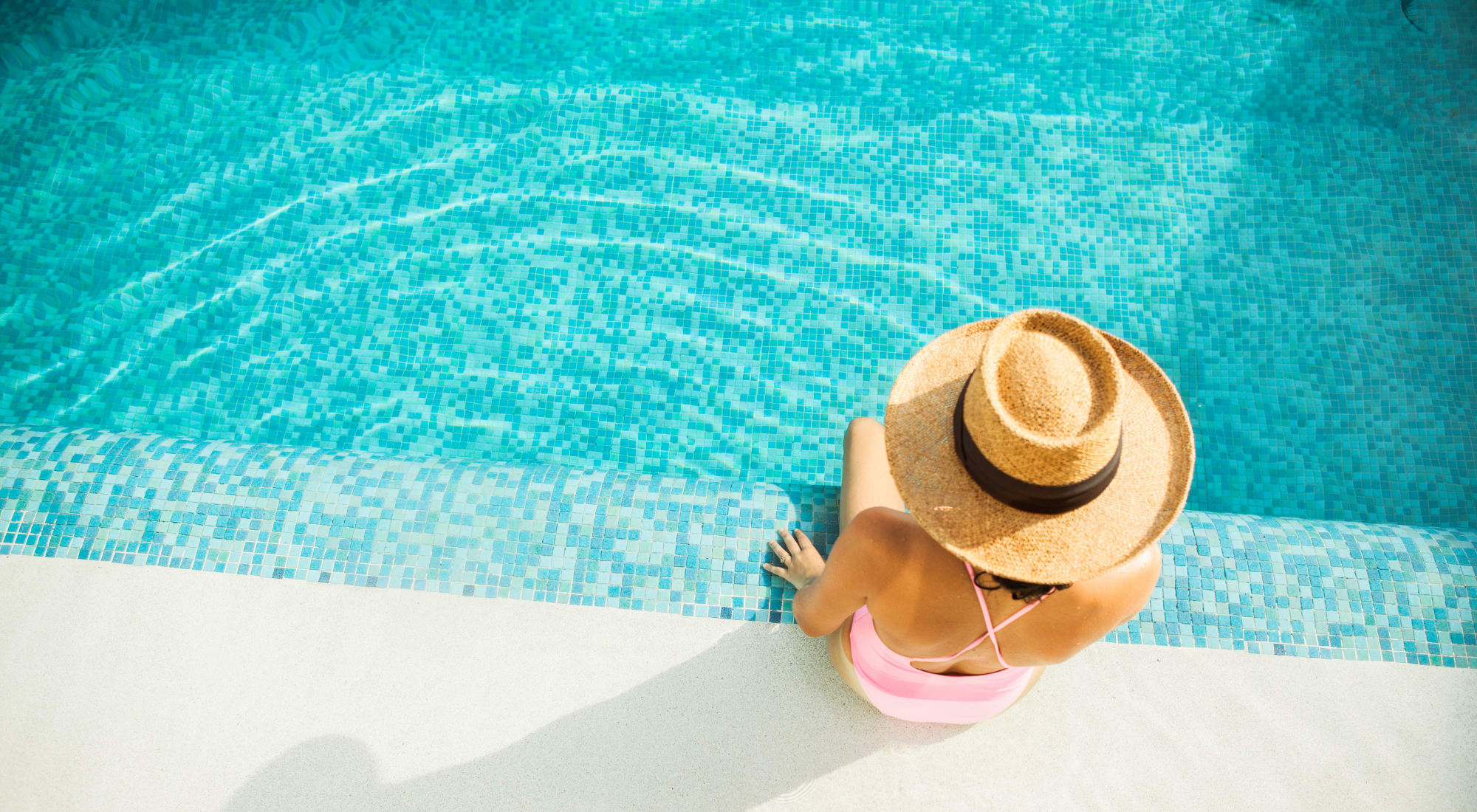 Aerial view of a woman in a wide-brimmed hat sitting by the edge of a pool at Fusion apartments in Jacksonville, Florida