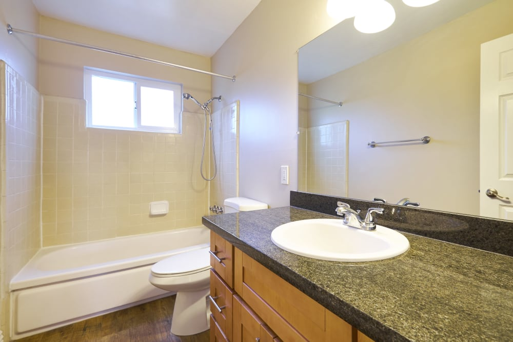 Bathroom with a large vanity mirror and an oval tub at Palms at the Pruneyard in Campbell, California