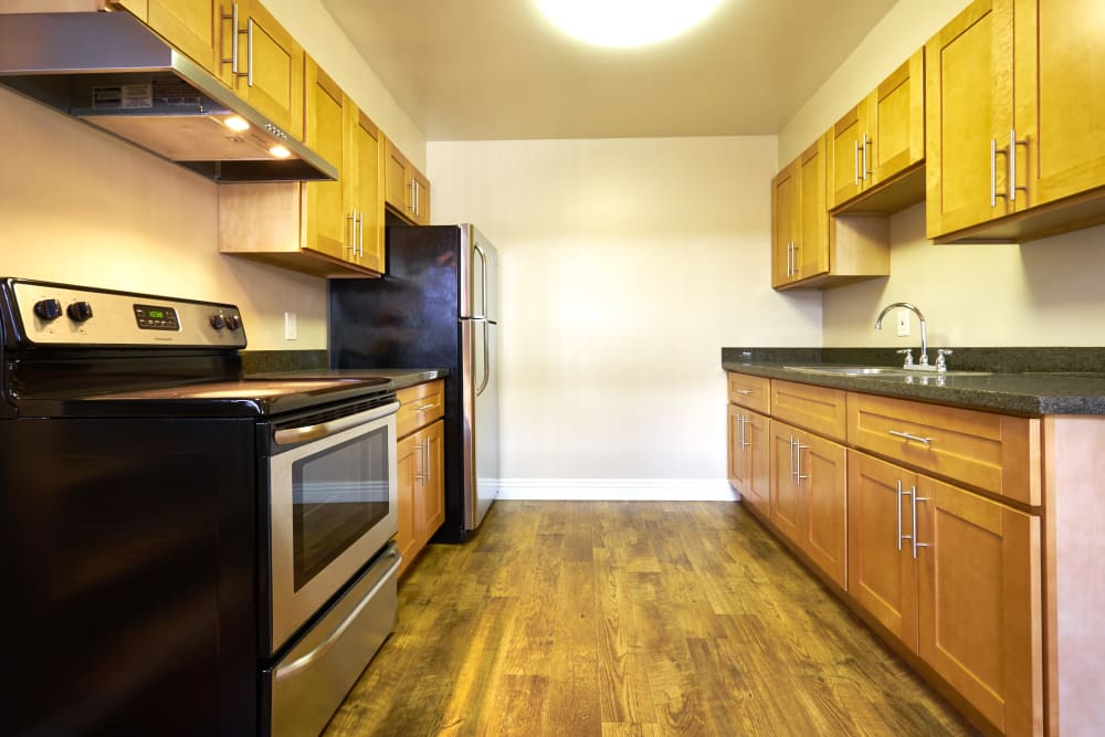 Kitchen with a black stove top and wooden cabinets at Palms at the Pruneyard in Campbell, California