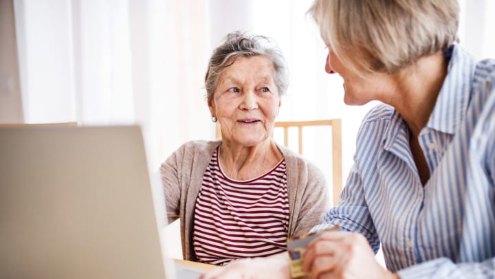 Senior woman with adult daughter on lap top