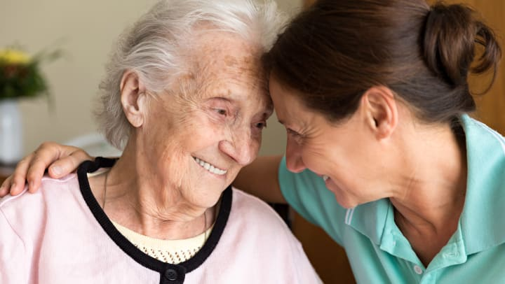 Elderly woman looking at younger woman leaning on each others foreheads.