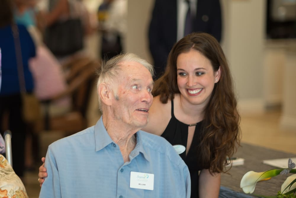 Staff member checking in on a resident at an event at Inspired Living in Sugar Land, Texas