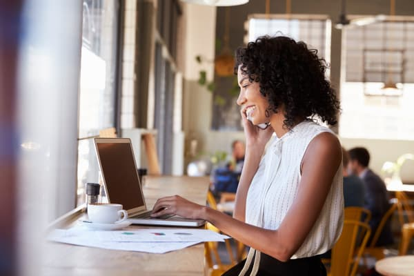 Woman with her computer and a cup of coffee at Bunting Management Group, Inc. in Eugene, Oregon