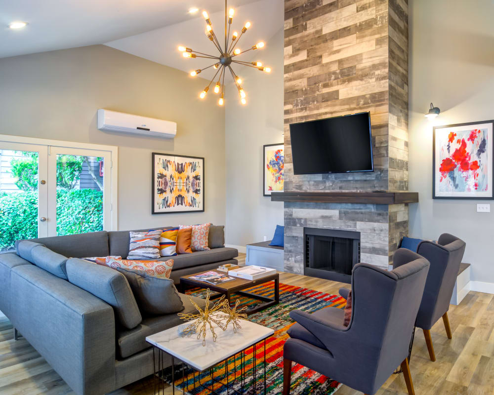 Resident lounge area with a fireplace and flatscreen TV in the clubhouse at Sofi at Somerset in Bellevue, Washington
