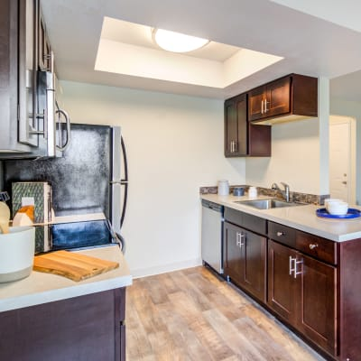 Modern kitchen with granite countertops and a breakfast bar in a model home at Sofi Lake Oswego in Lake Oswego, Oregon