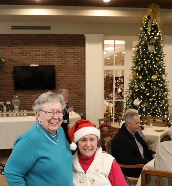 Residents at our senior living community in Madison, AL smiling by the Christmas tree