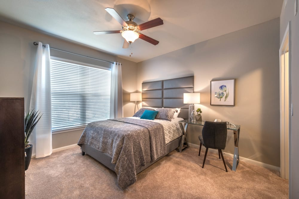 Model home's master bedroom with plush carpeting and a ceiling fan at Olympus Las Colinas in Irving, Texas