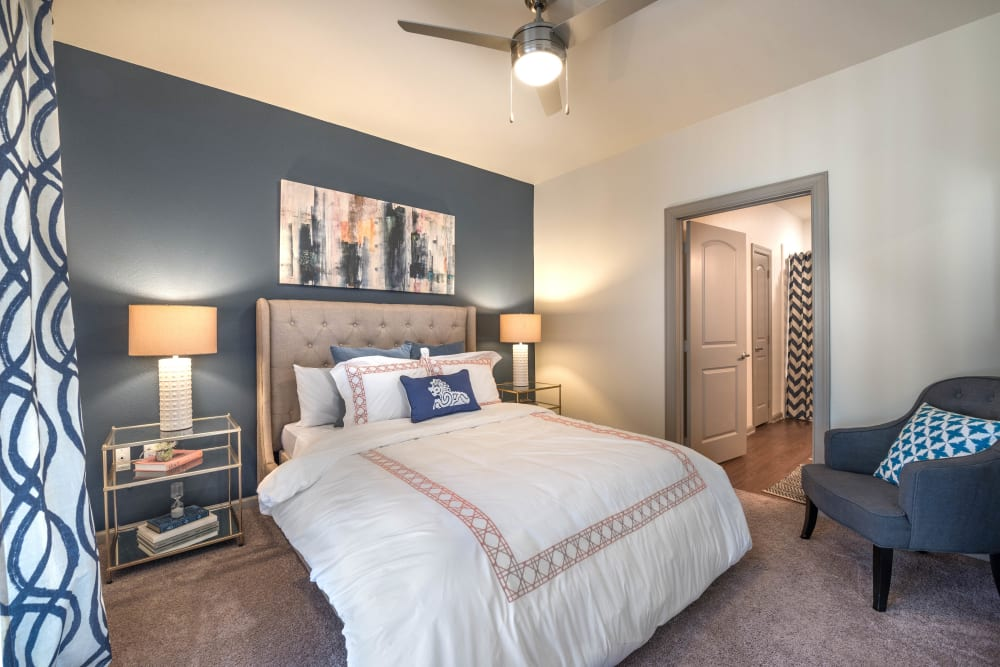 Model home's master bedroom with an accent wall and a ceiling fan at Olympus Waterford in Keller, Texas