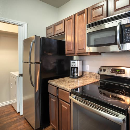 Gourmet kitchen with granite countertops and an adjacent laundry room in a model home at Olympus Willow Park in Willow Park, Texas