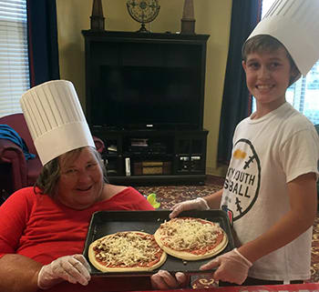 A resident and child making pizzas