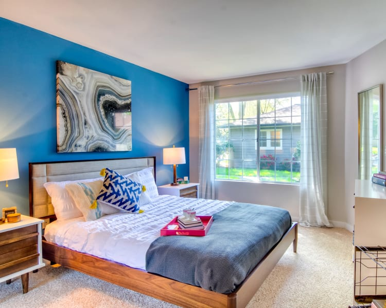 Well-furnished bedroom with an accent wall and draped windows in a model home at Sofi at Murrayhill in Beaverton, Oregon