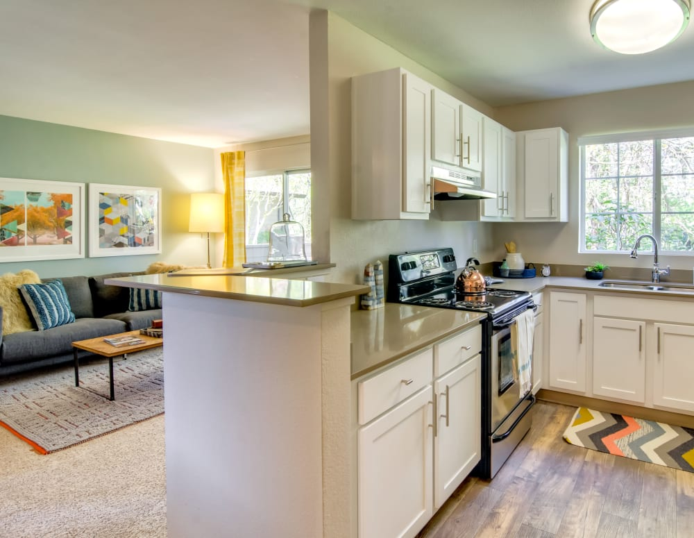 Modern kitchen with quartz countertops looking into the living area of a model home at Sofi at Murrayhill in Beaverton, Oregon