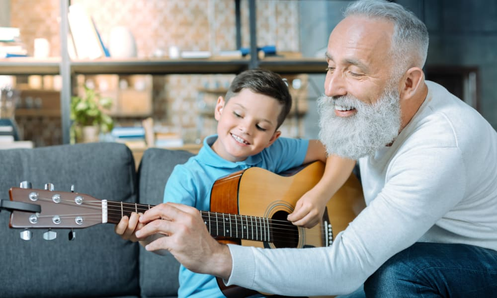 A resident and a child learning to play the guitar at Amaran Senior Living in Albuquerque, New Mexico.