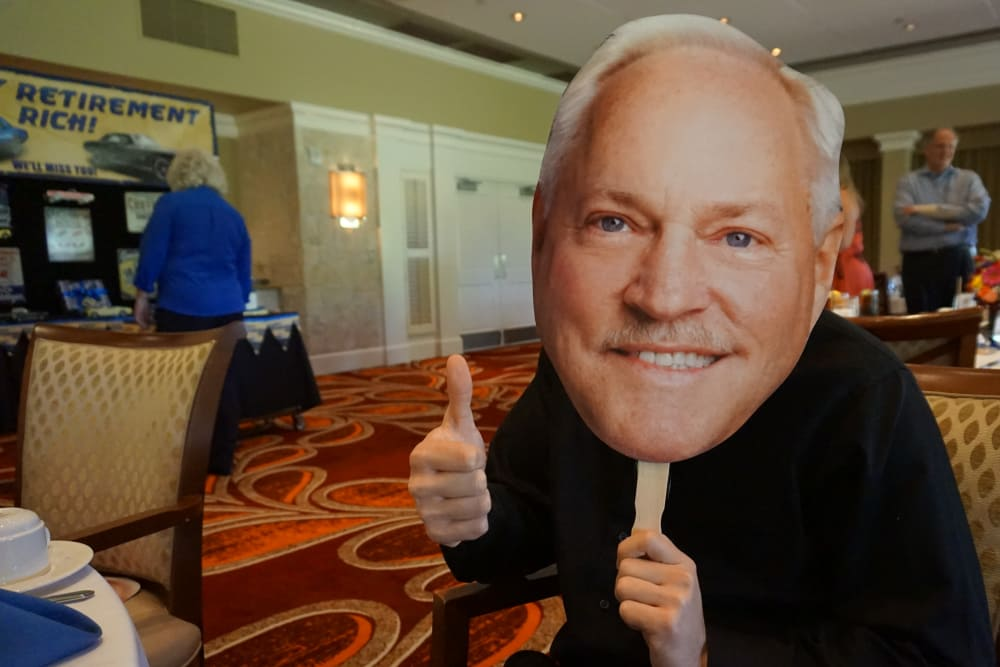 A man holding a giant cut out over his face at Discovery Senior Living in Bonita Springs, Florida