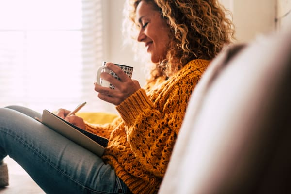 Resident writing in her diary about how much she loves her new home at Slate Ridge at Fisher's Landing Apartment Homes in Vancouver, Washington