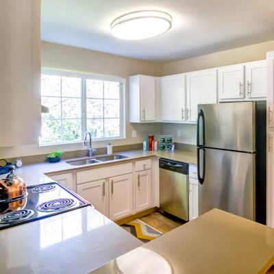 Bright kitchen with stainless-steel appliances and ample cupboard storage in a model home at Sofi at Murrayhill in Beaverton, Oregon