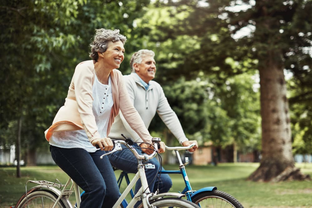 Two residents riding a bike near Merrill Gardens.