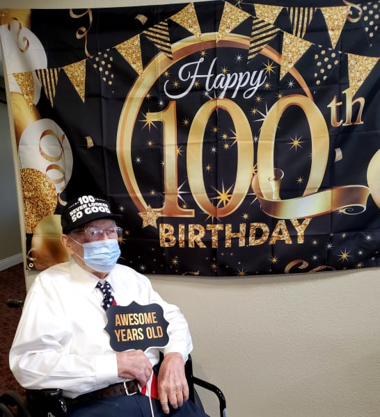 Frank, a Siena Hills resident, takes a photo in front of his 100th birthday sign.