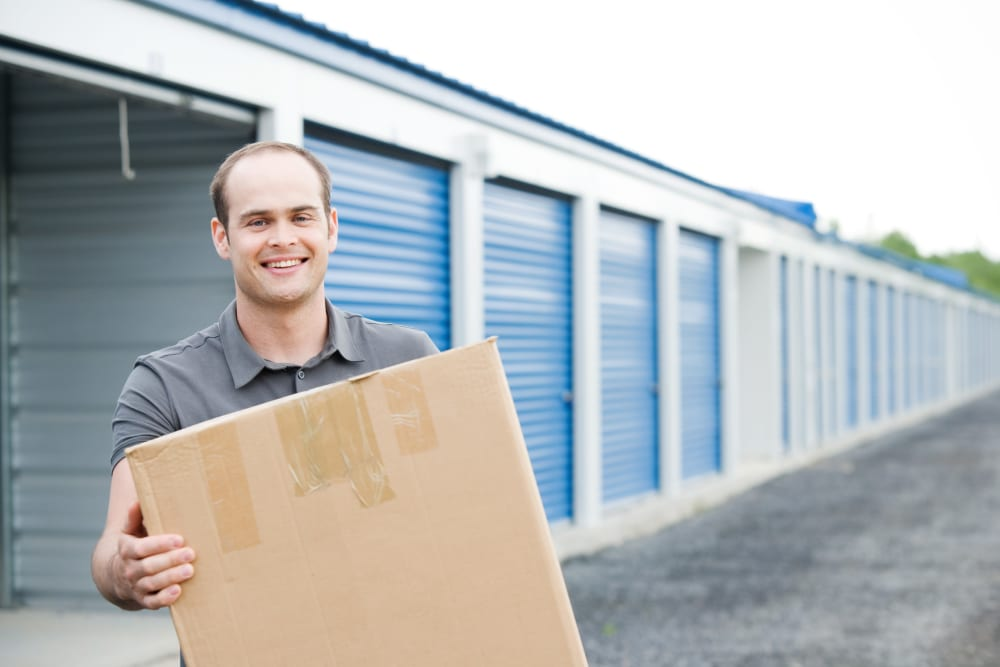 A man with a box in front of an easy-lift door unit at Battle Ground Mini Storage in Battle Ground, Washington